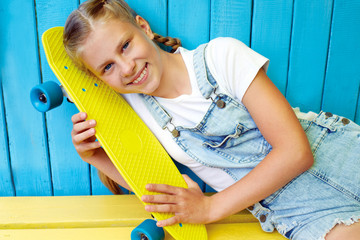 Нappy, laughing child wearing cool fashion clothing posing with colorful skateboard against blue wall, urban style.
