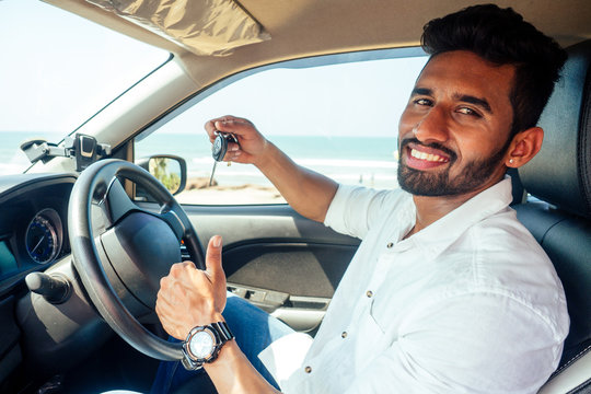 travel vacation happy indian man in white shirt collar buying new car and showing the key, sitting in car on beach sea india octan Goa .a trip to the beach in car