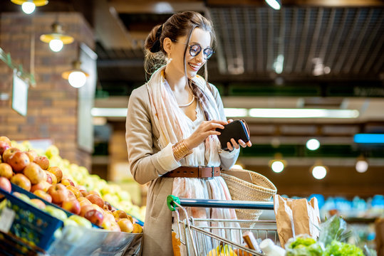 Young woman getting wallet with money while buying food in the supermarket