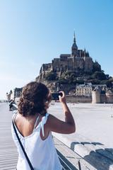Woman taking a photo in Mont Saint-Michel