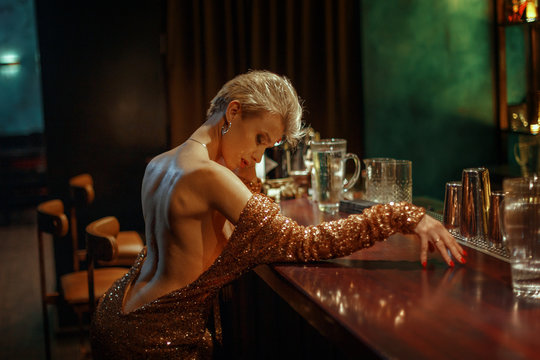 Young beautiful blonde girl in a luxurious golden sexy dress sitting at the bar.