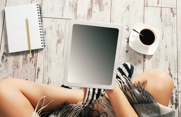 Woman with a cup of coffee, notepad and tablet