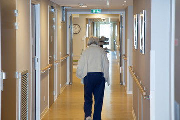 portrait of elderly woman walking down hallway in retirement home background