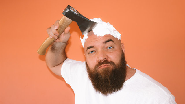 Portrait of bearded hipster man shaving his head with an ax (axe, hatchet) looking to the camera, orange background