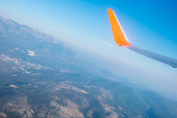 Airplane wings in the blue sky and a mountains view scene. Travel and adventure.