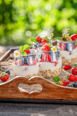 Healthy granola with berries and yoghurt in jar