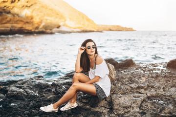 Fotobehang Pretty long hair tourist girl relaxing on the stones near sea.