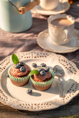 Brown cupcake served with coffee in garden