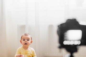 Beautiful baby toddler in front of the camera vlogging or blogging indoors