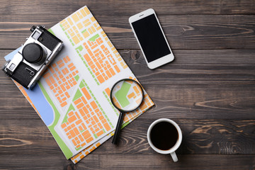 Composition with city map, photo camera, magnifier and mobile phone on wooden table. Travel concept
