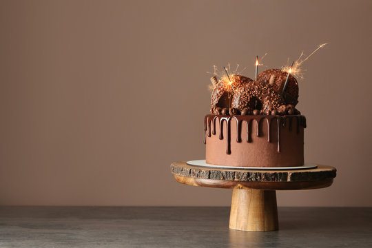 Sweet chocolate cake with sparklers on table against color background