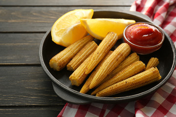 Frying pan with tasty corn cobs, lemon and sauce on wooden table