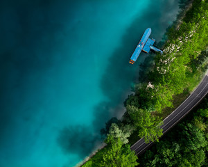 Blue lake waters and turist boat, aerial view
