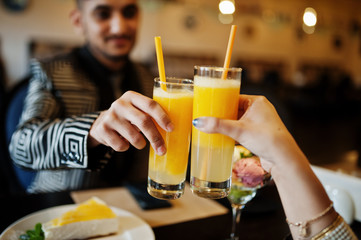 Close up hands of lovely indian couple in love, sitting on restaurant and cheers together by orange juice. Fototapete