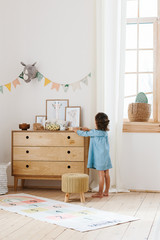 Little girl wearing light blue dress playing in children room scandinavian style.