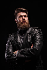 Portrait of Handsome bearded man wearing a leather jacket with serious expresion over black background