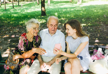 Young girl is making a selfie with her grandma and grandpa in the park. Old couple with granddaughter watching video on smartphone. Modern technologies and happy emotions and laugh. Summer family walk