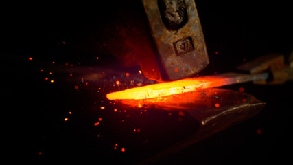 MACRO: Red hot piece of metal is held by tongs and struck by a big hammer.