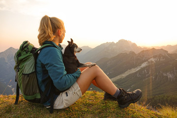 CLOSE UP: Girl sits on mountaintop and pets her dog while observing the nature.