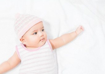 Asian baby wear pink knitting hat on white towel background