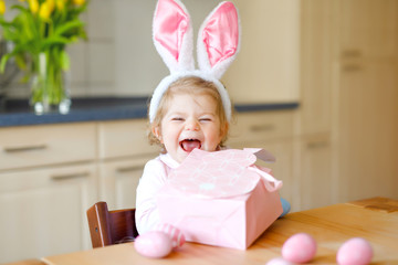Cute little toddler girl wearing Easter bunny ears playing with colored pastel eggs. Happy baby child unpacking gifts. Adorable healthy smiling kid in pink clothes enjoying family holiday