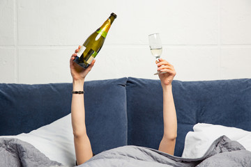 Hands of woman with bottle and glass of champagne in bed