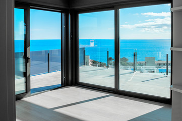 Empty rooms in a new house with large windows overlooking the sea. Automatic blinds. Glass partition terrace. Wall mural