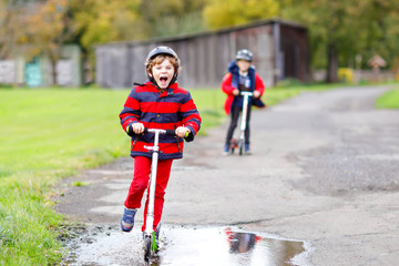 Two little kids boys riding on push scooters on the way to or from school. Schoolboys of 7 years driving through rain puddle. Funny siblings and best friends playing together. Children after school