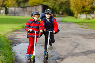 Two little kids boys riding on push scooters on the way to or from school. Schoolboys of 7 years driving through rain puddle. Funny siblings and best friends playing together. Children school out.