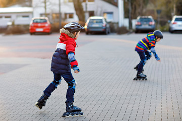 Two little kids boys skating with rollers in the city. Happy children, siblings and best friends in protection safety clothes. Active schoolboys making sports and learning to skate on inline skater.