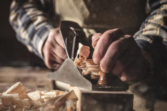 Hände eines Schreiners bei der Arbeit mit dem Hobel