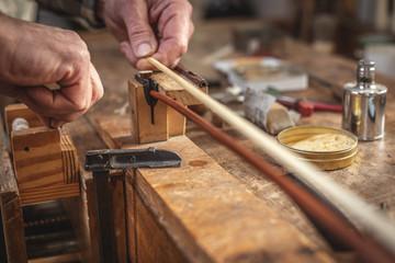 Hände eines Geigenbauers beim Einsetzen der Bogenhaare