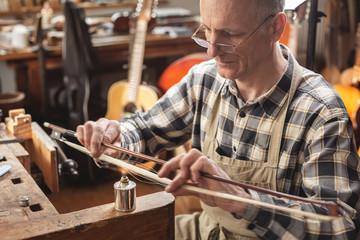 Instrumentenbauer beim Erhitzen von Bogenhaar
