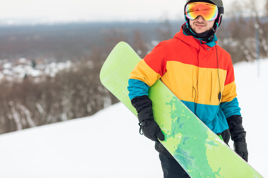 athlete holding a snowboard in hands during winter holiday. Closeup view.free time, spare time, copy space