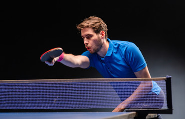 Handsome young man playing ping pong table tennis