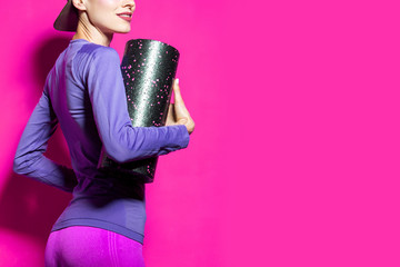 Bright fitness woman. Sport fashion. Funny sport fitness woman with foam roller isolated over bright background