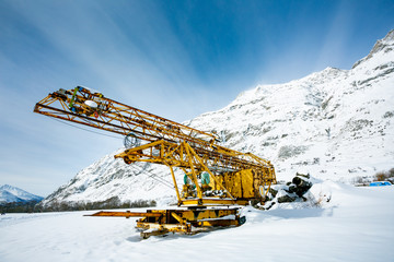 Abandoned yellow metal construction or construction equipment on the background of snowy mountains and blue sky