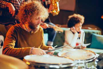 Caucasian talented drummer playing drums. In background mixed race woman having earphones on ears and smiling. Home studio interior.