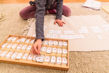 Student girl hand using cards with letters to compose words, sitting on the classroom floor of her montessori school.