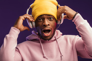 Studio portrait of surprised, shocked DJ, standing open-mouthed with headphones on yellow knitted hat on head looking at camera with disbelief and surprise, omg concept.