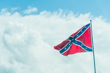 Confederate flag under a blue sky with clouds in Florida