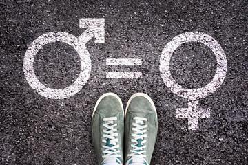 Sneaker shoes on asphalt background with gender symbols, gender equality education concept