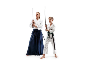 Man and teen boy fighting at Aikido training in martial arts school. Healthy lifestyle and sports concept. Fightrers in white kimono on white background. Karate men with concentrated faces in uniform.