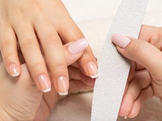 Woman gets manicure procedure in a spa salon. Beautiful female hands.
