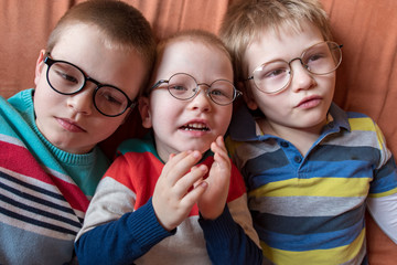 Three brothers in bright colored clothes posing in front of camera with glasses for vision. Children are very similar to each other and happy together. Preschoolers on vacation in their home