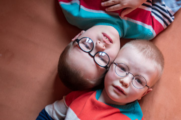 Two brothers in bright colored clothes posing in front of camera with glasses for vision. Children are very similar to each other and happy together. Preschoolers on vacation in their home