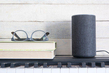 Alexa Echo smart speaker for IoT and home automation on a piano next to some books against a wooden background. Empty copy space for Editor's text.