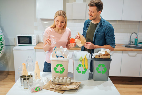 Waste sorting at home. Smiling young couple putting plastic, paper, other waste in garbage bio bins in the kitchen