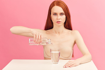 Determined anorexic woman with long ginger hair , sitting in underwear drinking only water. Starvation