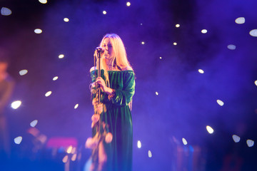 Young blond woman singer in concert light